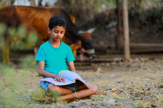Cute indian child reading his book at cattle shed