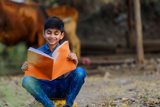 Cute indian child reading his book
