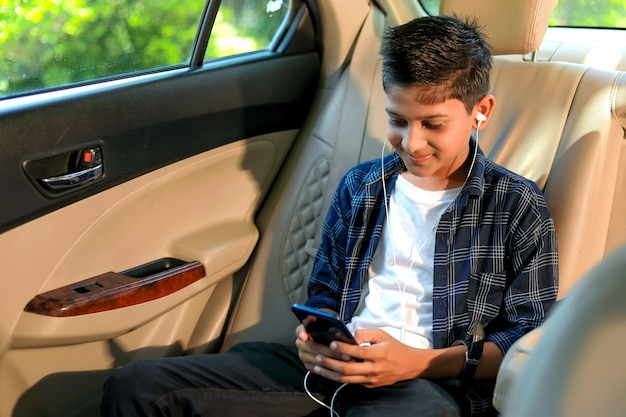 Cute indian child sitting in car and using smart phone and headphones gadget