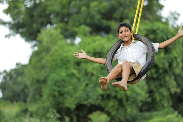 Милый индийский ребенок сидит на качелях в шинах
