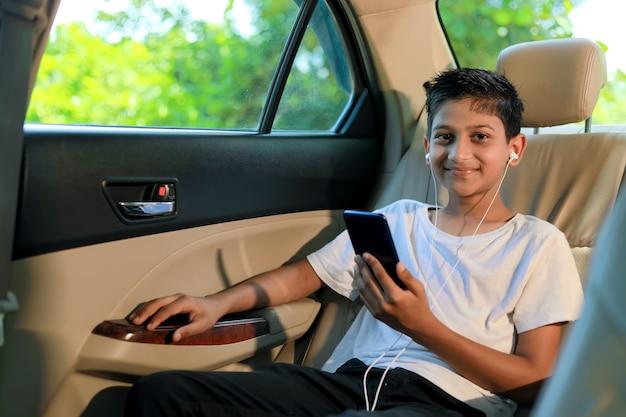 Милый индийский ребенок сидит в машине и использует гаджет для смартфонов и наушников
