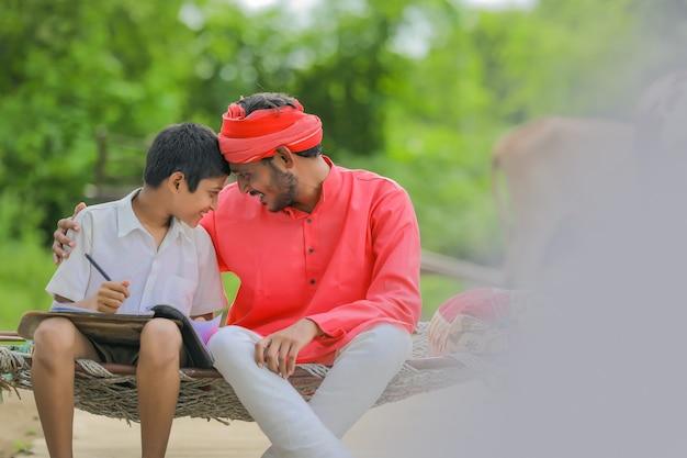 집에서 그의 아버지와 함께 공부하는 귀여운 인도 아이