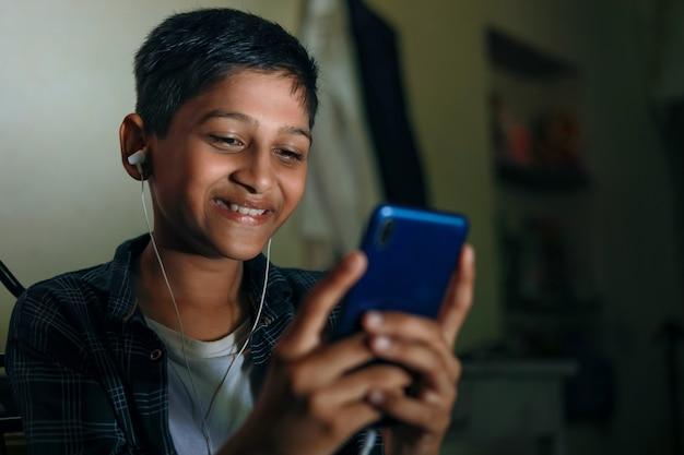 Милый индийский ребенок, использующий смартфон и наушники