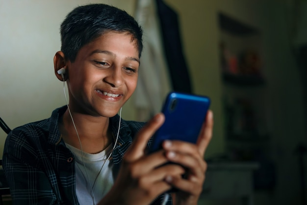 Cute indian child using smart phone and headphones gadget
