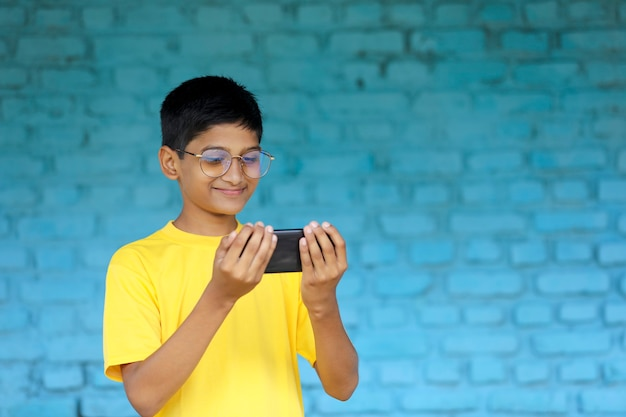 Cute indian child using smartphone. online education concept