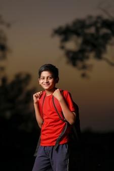 通りに袋袋を持つかわいいインドの子供