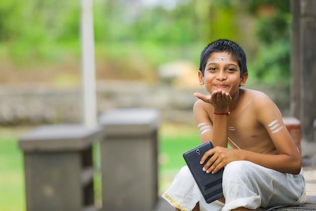 Милый индийский ребенок с планшетом