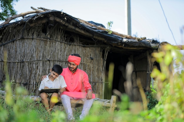 Cute indian farmer child studying with his father at home