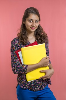 Cute indian girl student with books and folders in hands. young woman teacher.