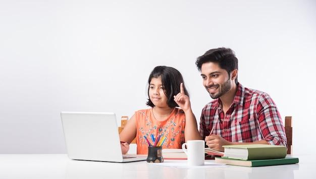 Милая индийская девочка с отцом учится или делает домашнее задание дома, используя ноутбук и книги - концепция онлайн-обучения