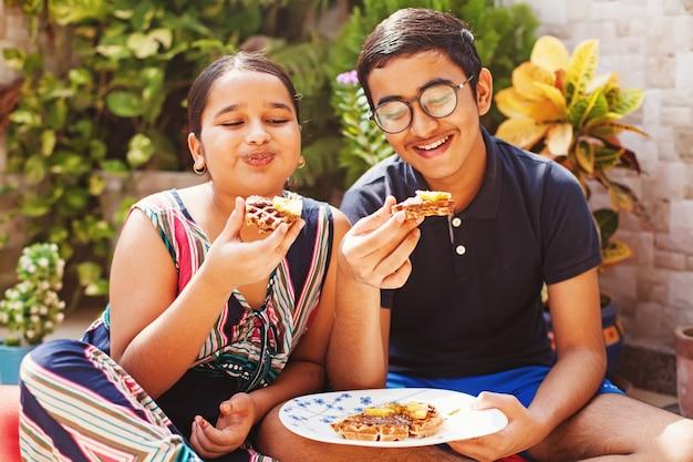 맛있는 초콜릿 와플을 먹는 귀여운 인도 아이들