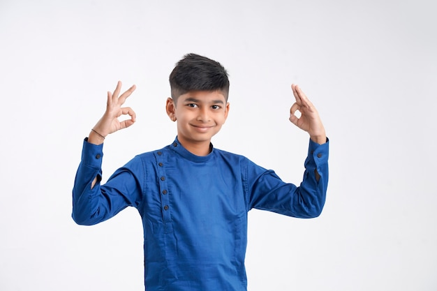 Cute indian little boy in ethnic wear and showing expression on white