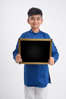 白い背景の上にコピースペースで黒板を示すかわいいインドの小さな男の子