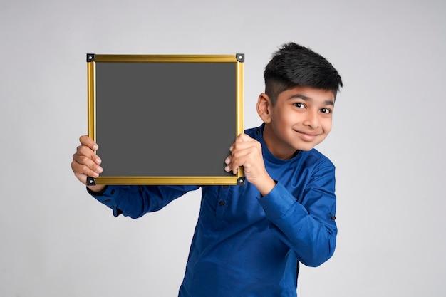 흰색 배경 위에 복사 공간 블랙 보드를 보여주는 귀여운 인도 소년
