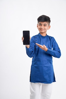 Cute indian little boy showing smart phone screen on white