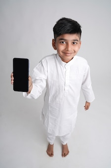 Милый индийский маленький мальчик показывает экран смартфона с копией пространства на белом фоне