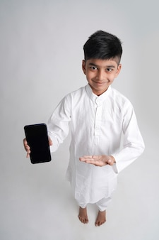 Cute indian little boy showing smart phone screen with copy space over white background
