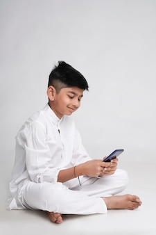 Cute indian little boy using smart phone