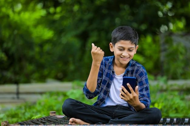 Милый индийский маленький ребенок в восторге от использования смартфона