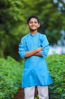 전통 의상을 입고 농업 분야에 서 있는 귀여운 인도 어린 아이