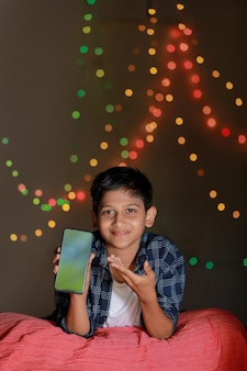 Cute indian little child showing smart phone screen and giving expression