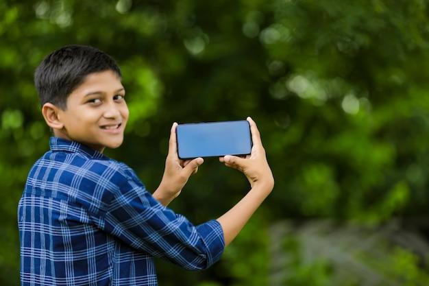 Милый индийский маленький ребенок показывает смартфон с пустым экраном