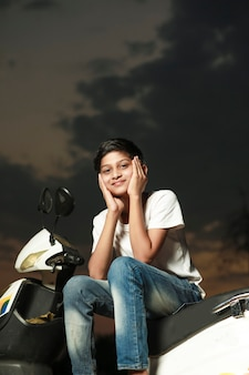 Cute indian little child sitting on scooter and giving multiple expression