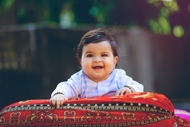 Cute indian little child smiling and playing in front of house