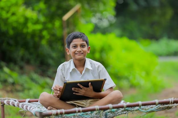 Милый индийский маленький ребенок учится дома