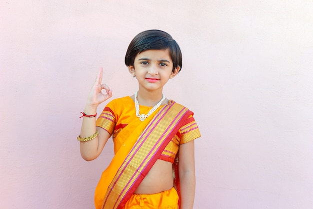 Cute indian little girl in tradition dress pointing