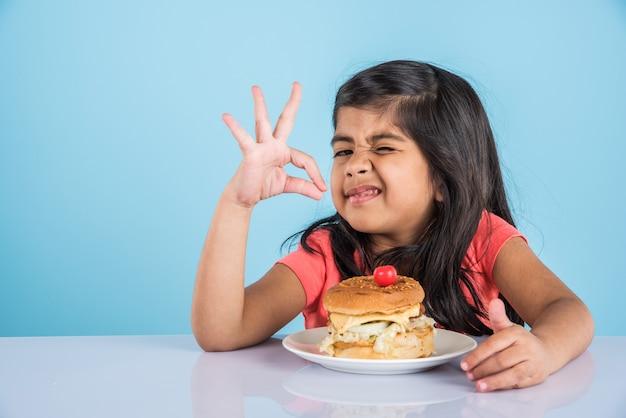 Милая индийская или азиатская маленькая девочка ест вкусный гамбургер, сэндвич или пиццу в тарелке или коробке. стоя изолированные на синем или желтом фоне.