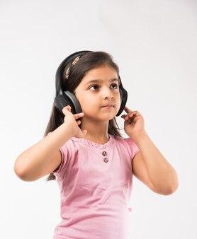 白で隔離のワイヤレスヘッドフォンで音楽を聴いてかわいいインドまたはアジアの小さな女の子