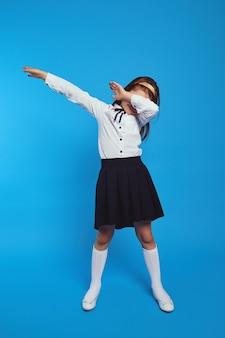 Милая трудолюбивая школьница в униформе на синем бумажном фоне стены
