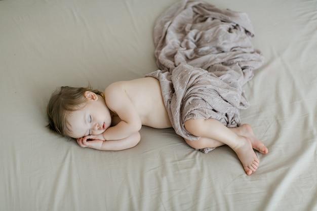Милый ребенок девочка спит в постели. вид сверху