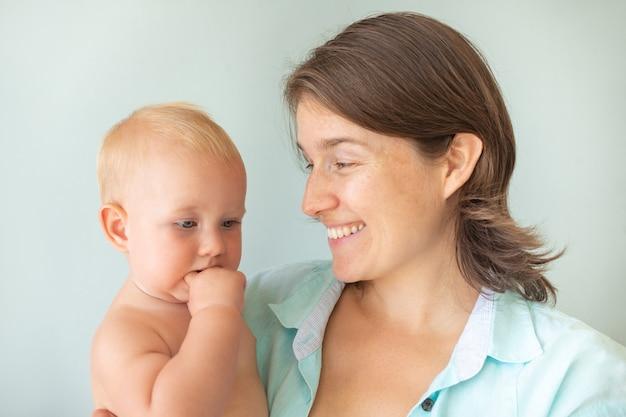 灰色の背景に母親の手でかわいい幼児の赤ちゃん。愛を込めて赤ちゃんを抱き締める母親。母性の概念。無条件の愛。
