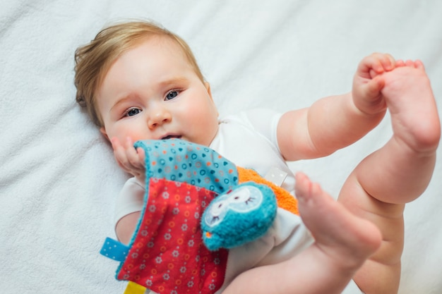 Cute infant teething baby biting and chewing on calming soother toy.