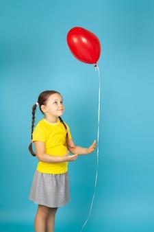 노란색 티셔츠에 귀여운 관심있는 소녀가 문자열로 빨간 하트 모양의 풍선을 보유하고 있습니다.