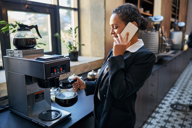 Симпатичная международная женщина с улыбкой на лице, стоя в полу-положении возле кофемашины