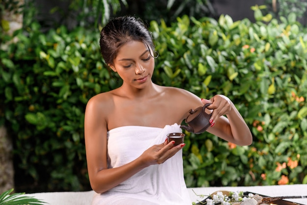 A cute interracial model sits in a white terry towel on a massage couch on which stands a tray with white flowers and a basket and pours a drink from a clay teapot into a small clay cup