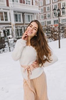 白いウールのセーター、冬には通りを歩いて軽いスカートの長いブルネットの髪を持つかわいいうれしそうな素晴らしい若い女性。陽気な気分、前向きな真の感情、雪。