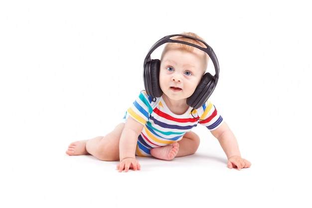 Cute joyful baby boy in colorful shirt and headphones on head