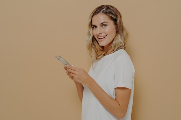 Милая радостная студентка с помощью мобильного телефона смотрит в камеру, проверяя ленту новостей своей учетной записи в социальной сети или просматривая интернет на мобильном телефоне. концепция людей и современных технологий