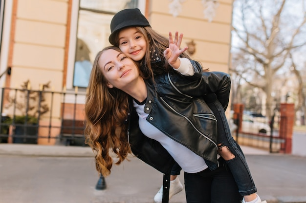 Cute joyful girl in black hat waving hand, riding on mother's back during walk around city. outdoor portrait of lovely woman in trendy jacket carrying daughter and posing in front of building.