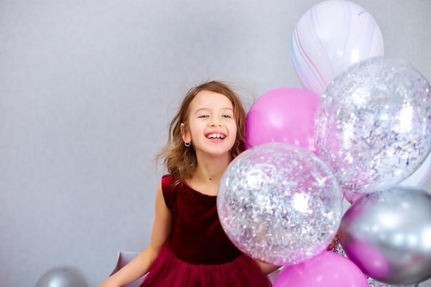 Милая радостная маленькая девочка в розовом платье и шляпе играет с воздушными шарами дома, на день рождения, стримеры