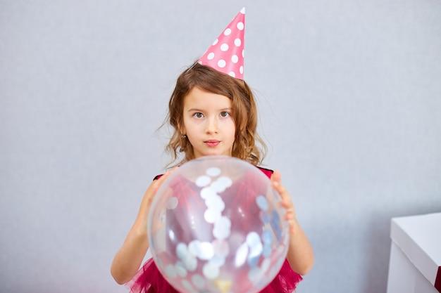 Милая, радостная маленькая девочка в розовом платье и шляпе играет с воздушными шарами на домашней вечеринке по случаю дня рождения