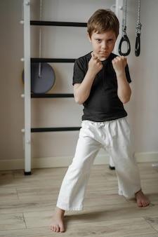 Cute karate boy standing in white kimono pants and black t-shirt