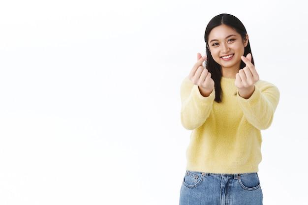 Simpatica ragazza asiatica kawaii in maglione giallo che mostra cuori coreani con le dita e sorride, ride sciocca, posa contro il muro bianco felice e gioiosa, promuove prodotti per il trucco dell'asia