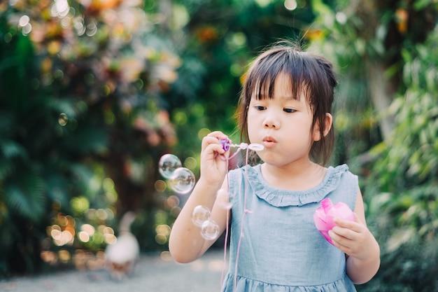 Cute kid blowing bubbles soap in the  garden. Premium Photo