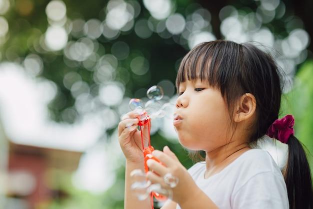 Cute kid blowing bubbles soap in the garden.