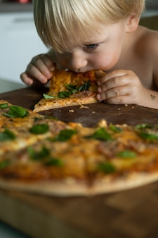 Cute kid boy eating home made pizza at kitchen at home.